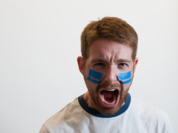 man with blue tape on face, screaming